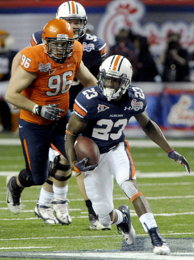 Auburn running back Onterio McCalebb (23) rushes as Virginia defensive tackle Nick Jenkins (96) pursues during the fourth quarter of the Chick-fil-A Bowl NCAA college football game, Saturday, Dec. 31, 2011, in Atlanta. Auburn won 43-24. (AP Photo/John Amis)