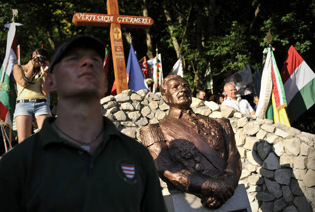 This photo taken June 16, 2012 shows a member of the controversial far-right Hungarian Guard standing by the unveiled bust of Admiral Miklos Horthy, Hungary's WWII ruler in Csokako, Hungary. Erecting a memorial for the controversial Horthy was welcomed by the Hungarian right wing, while the act was widely criticized by the country's liberal society. (AP Photo/Bela Szandelszky)