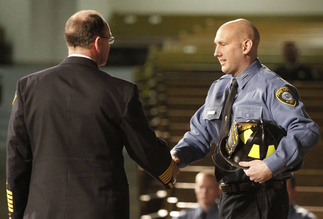 Chief Keith Bryant, left, congratulates Kevin Valdez during the Oklahoma City Fire Department's recruit class of 2011-2 graduation.