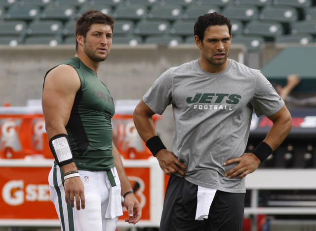ADVANCE FOR WEEKEND EDITIONS, AUG. 25-26 - FILE - This Aug. 10, 2012 file photo shows New York Jets quarterbacks Tim Tebow, left, and Sanchez during warms up prior to an NFL preseason football game against the Cincinnati Bengals, , in Cincinnati. Two-quarterback systems have rarely worked, but the Jets plan to test that theory with Sanchez and Tebow this season. (AP Photo/David Kohl, File)