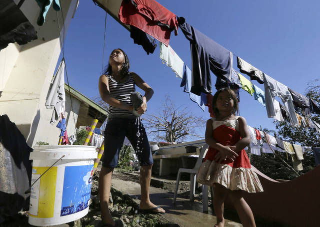Typhoon evacuees dry their clothes at an evacuation center at Maparat township, Compostela Valley in southern Philippines Saturday Dec. 7, 2012. Search and rescue operations following typhoon Bopha that killed nearly 600 people in the southern Philippines have been hampered in part because many residents of this ravaged farming community are too stunned to assist recovery efforts, an official said Saturday. (AP Photo/Bullit Marquez)