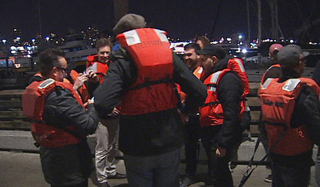   This image provided by KTVU-TV shows some of the 22 rescued passengers on the pier Friday Oct.12, 2012 in San Francisco. A U.S. Coast Guard spokesman said the wine-tasting boat, Neptune hit a shoal near Alcatraz Island and began sinking. Nearly two dozen people who were enjoying a boat ride on what&#039;s billed as San Francisco Bay&#039;s only &quot;floating wine tasting room&quot; are OK after their vessel hit a shoal near Alcatraz Island and started sinking Friday night. U.S. Coast Guard spokesman Lt. j.g. Josh Dykman says the 45-foot Neptune hit the shoal around 8:42 p.m. and started taking on water after the impact left a 1-foot gash in the side of the boat. The boat&#039;s captain tried to get it back to Pier 39, where the boat is docked, but the captain had difficulty navigating the vessel and it started sinking. Dykman says three Coast Guard boats took all 22 passengers and crewmembers off the vessel and brought them back to the pier. There were no injuries.(AP Photo/KTVU-TV)   