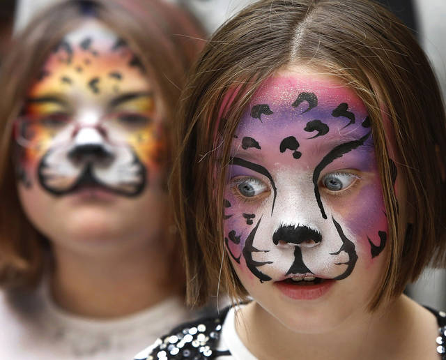 Rachel Dedmon, 8, right,  has a shocked look on her painted face when she and best friend Savannah Lee, 8, are told by a Platt College representative that the red sauce she gives them  to dip merengue bones into is made with blood . The pastry chef was teasing  the girls about the dip and quickly explained to the girls it is actually a cherry based sauce.  Residents of Moore were invited to celebrate the Mexican tradition of honoring deceased loved ones at the Moore Public Library's Day of the Dead Culture Festival on  Saturday, Oct. 27, 2012. Activities included Day of the Dead bread and merengue bones prepared by Platt College students and staff, musical performances, face painting, storytelling and crafts.  Photo by Jim Beckel, The Oklahoman