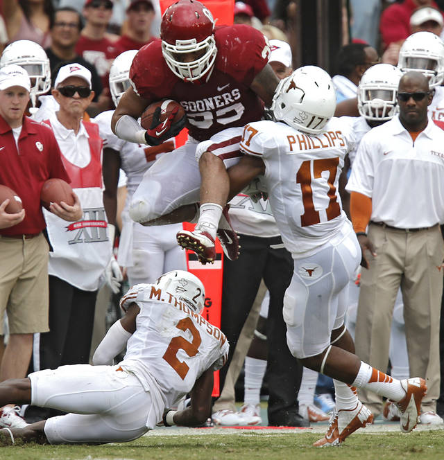 OU's Trey Millard (33) leaps over UT's Mykkele Thompson (2) and Adrian Phillips (17) during the Red River Rivalry college football game between the University of Oklahoma (OU) and the University of Texas (UT) at the Cotton Bowl in Dallas, Saturday, Oct. 13, 2012. Photo by Chris Landsberger, The Oklahoman