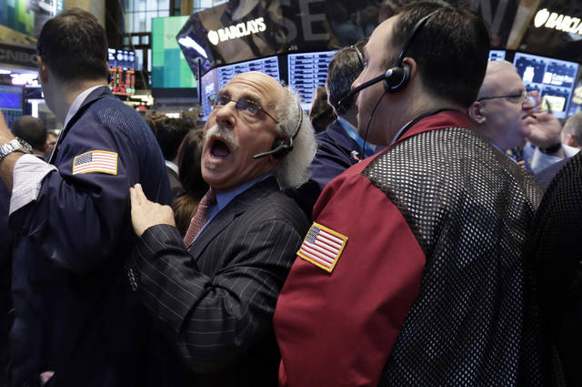 Trader Peter Tuchman, center, works on the floor of the New York Stock Exchange, Friday, Jan. 25, 2013. Stocks are opening higher on Wall Street ahead of what is expected to be more upbeat data on housing from the government. (AP Photo/Richard Drew)