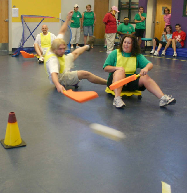 Slap Shot! Kyle Weatherly fights for balance on his roller pad as he makes a shot down the floor past his teammate Lynne Bates. Roller Hockey was one of the team building competitions held during the McCarty Center's Olympic games played during employee appreciation month in August. In the goal is Patrick Grose.<br/><b>Community Photo By:</b> Greg Gaston<br/><b>Submitted By:</b> Greg,