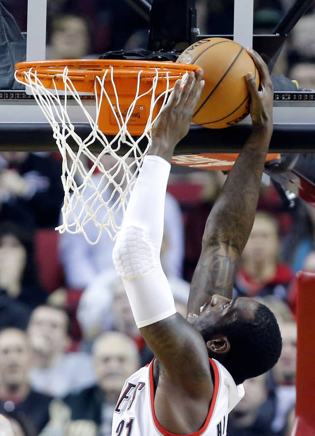 Portland Trail Blazers center J.J. Hickson gets the ball stuck between the basket rim and backboard on an alley-oop dunk attempt during the first quarter of an NBA basketball game against the Phoenix Suns in Portland, Ore., Saturday, Dec. 22, 2012. (AP Photo/Don Ryan)