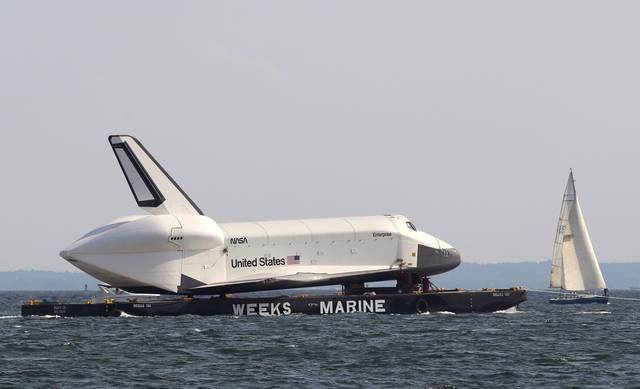 A sailboat passes the space shuttle Enterprise as it is towed past Coney Island in New York, Sunday, June 3, 2012. The prototype space shuttle that arrived in New York City by air earlier this spring is on the move again, this time by sea, to it's final resting place at the Intrepid Sea, Air and Space Museum on the west side of Manhattan. (AP Photo/Seth Wenig)