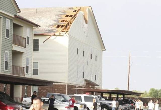 Residents mill around the parking lot at Independence Place Apartments on the east side of Lawton after a storm Monday ripped a hole in the roof. High winds and large hail caused 8,500 customers to lose power, according to PSO. (AP Photo/The Lawton Constitution,Brandon Neris)