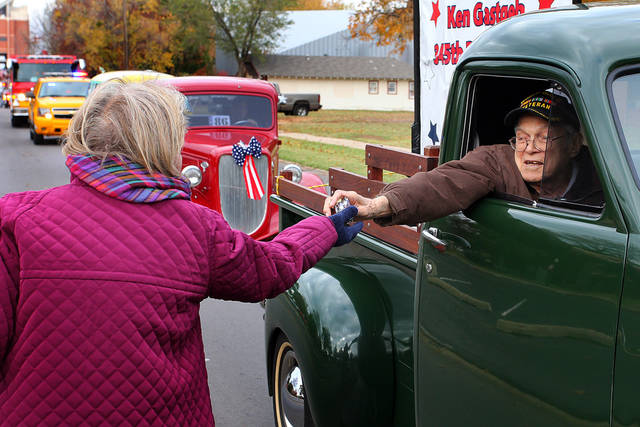 Ken Gastgeb, who served in the 345th Bomb Group during World War II gives candy to Linda Lockett, Norman City Councilwoman during the Veterans Day parade in Norman Sunday. PHOTO BY HUGH SCOTT FOR THE OKLAHOMAN ORG XMIT: KOD