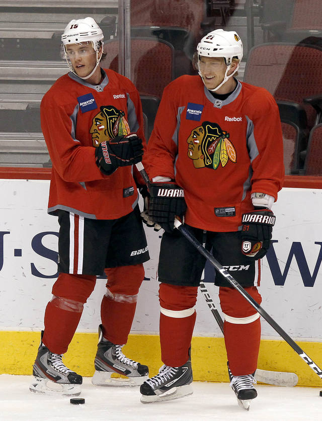 Chicago Blackhawks' Jonathan Toews (19) and Marian Hossa (81), of Slovakia, pause to chat during practice Wednesday, April 11, 2012, in Glendale, Ariz. The Blackhawks and the Phoenix Coyotes are scheduled to play Game 1 of an NHL hockey playoffs Western Conference opening-round series Thursday. (AP Photo/Ross D. Franklin)