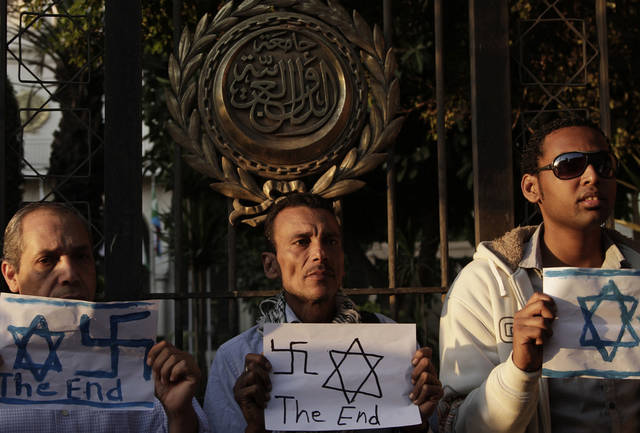 "Egyptians hold papers depicting Israeli flags and swastikas in front of the gate of the Arab League building during a protest in solidarity with Gaza after Israel launched its operation on Wednesday with the assassination of Hamas' top military commander in Cairo, Egypt, Thursday, Nov. 15, 2012. Egypt asked the United States to push Israel to stop its offensive against Hamas militants in the Gaza Strip, warning that the violence could ""escalate out of control,"" the Foreign Ministry said Thursday. (AP Photo/Nariman El-Mofty)"