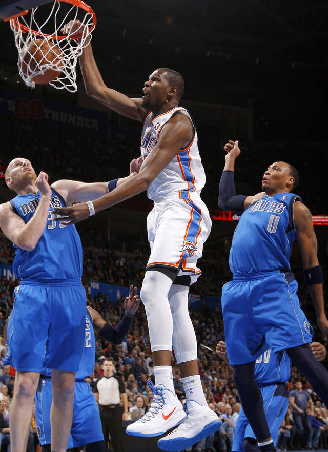 Oklahoma City's Kevin Durant (35) dunks the ball between Dallas' Chris Kaman (35) and Shawn Marion (0) during an NBA basketball game between the Oklahoma City Thunder and the Dallas Mavericks at Chesapeake Energy Arena in Oklahoma City, Thursday, Dec. 27, 2012.  Photo by Bryan Terry, The Oklahoman