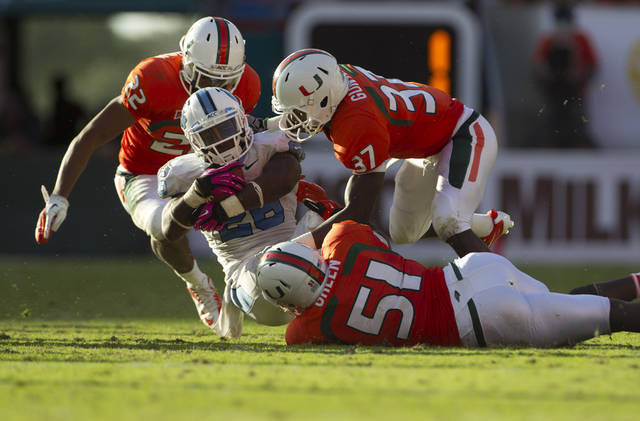 Miami playeres Kacy Rodgers II (22), Ladarius Gunter, (37) and Shayon Green (51) tackle North Carolina's Giovani Bernard (26) during the second half of an NCAA college football game in Miami, Saturday, Oct. 13, 2012. North Carolina won 18-14. (AP Photo/J Pat Carter)