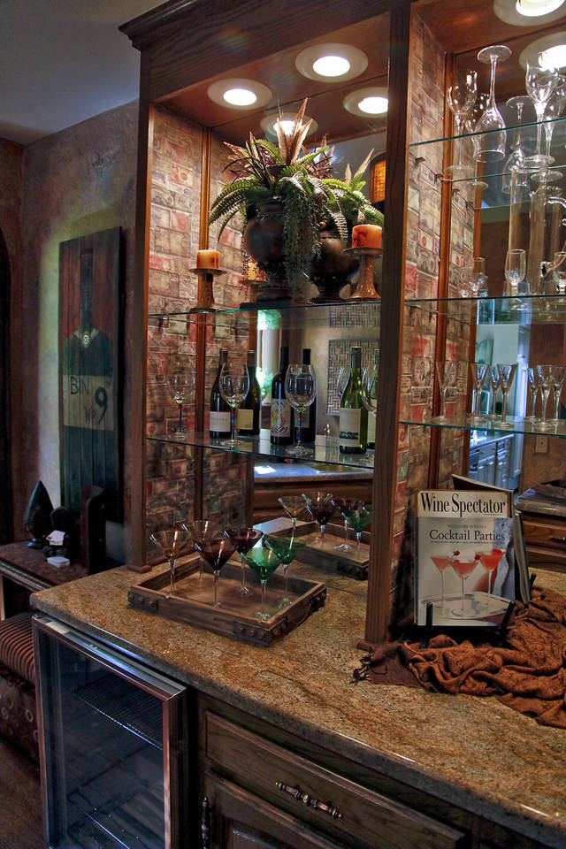 "The butler's pantry, called the ""Cash Bar"" was designed by designer Nora Johnson of Gold N Design. Johnson used copied foreign money as wallpaper behind the built in shelves. Photo by Chris Landsberger, The Oklahoman. <strong>CHRIS LANDSBERGER</strong>"