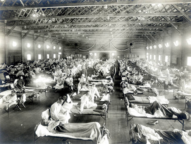 Medical workers tend to patients in an emergency hospital set up during the 1918 influenza pandemic in Camp Funston, Kan. Millions of people, including 675,000 in the United States, died of the Spanish flu. Photo courtesy of the National Museum