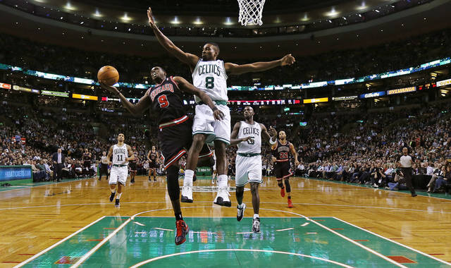 Chicago Bulls forward Luol Deng (9) tries to break free from Boston Celtics  forward Jeff Green (8) on a drive to the basket during the second half of an NBA basketball game in Boston Friday, Jan. 18, 2013. Deng left the game after the play. The Bulls won 100-99 in overtime. (AP Photo/Charles Krupa)