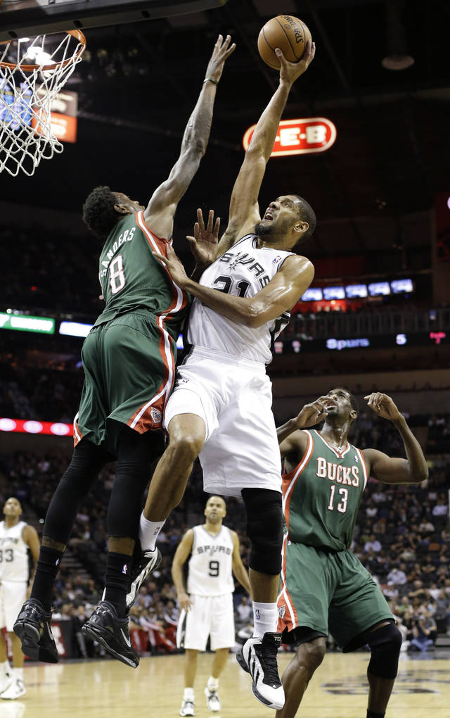 San Antonio Spurs' Tim Duncan, center, shoots over Milwaukee Bucks' Larry Sanders (8) as Ekpe Udoh (13) looks on during the first quarter of an NBA basketball game on Wednesday, Dec. 5, 2012, in San Antonio. San Antonio won 99-95. (AP Photo/Eric Gay)