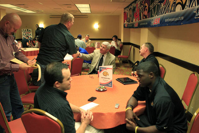 Southern Miss coach Ellis Johnson, center, shakes a reporter's hand after answering questions in the busy interview room during the NCAA college football Conference USA media day on Wednesday, July 25, 2012, in Dallas. (AP Photo/John F. Rhodes)