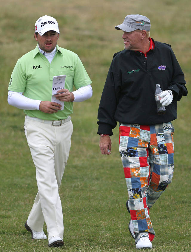 John Daly of the U.S., right, and Northern Ireland's Graeme McDowell walk down the 6th fairway during a practice round ahead of the British Open Golf Championship at Royal St George's golf course Sandwich, England, Wednesday, July 13, 2011. (AP Photo/Tim Hales)