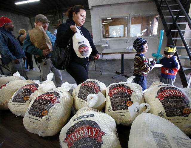 A woman and two children leave after picking up a Thanksgiving turkey and food basket on Nov. 19, 2012 at the Jesus House.