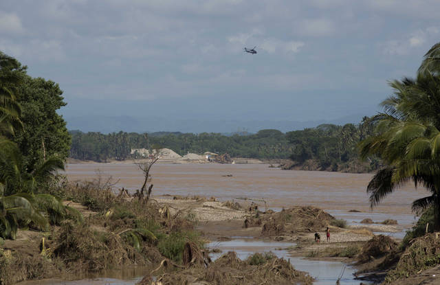 A federal police helicopter flies over a river, south of Acapulco, near the town of Lomas de Chapultepec, Guerrero state, Mexico, Wednesday, Sept. 18, 2013. With roads blocked by landslides, rockslides, floods and collapsed bridges, Acapulco was cut off from road transport after Tropical Storm Manuel made landfall on Sunday. The airport as well, was flooded. Emergency flights began arriving in Acapulco to evacuate at least 40,000 mainly Mexican tourists stranded in the resort city. (AP Photo/Eduardo Verdugo)