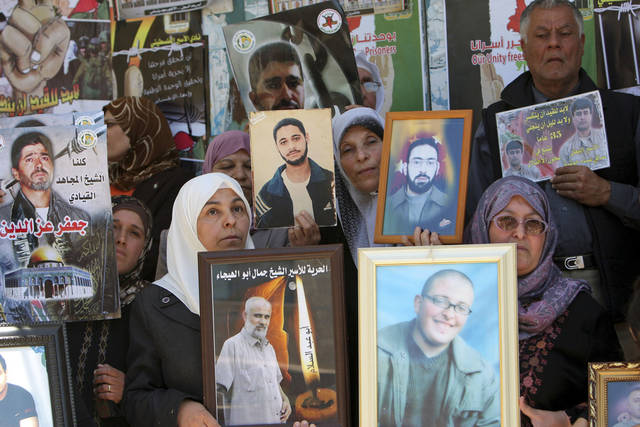 Palestinians hold photographs of prisoners jailed in Israel, during a rally marking the annual prisoners' day in the West Bank city of Jenin, Tuesday, April 17, 2012. The Israeli prison service said Tuesday hundreds of Palestinian prisoners have launched a hunger strike to mark the Palestinians' annual prisoners day. (AP Photo/Mohammed Ballas)