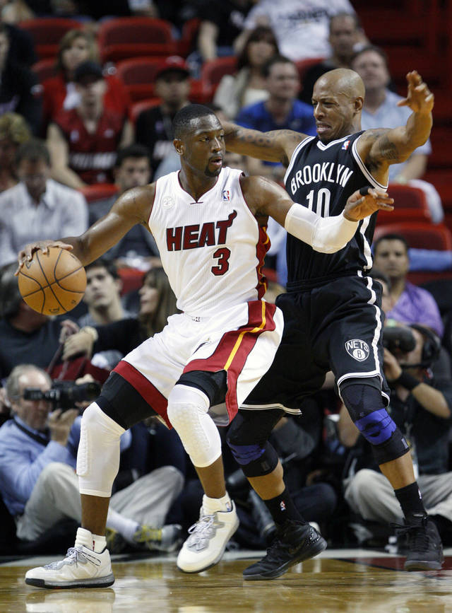 Miami Heat guard Dwyane Wade (3) drives past Brooklyn Nets guard Keith Bogans (10) during the second half of an NBA basketball game, Wednesday, Nov. 7, 2012 in Miami. Wade scored 22 points on 10 for 14 shooting as the Heat defeated the Nets 103-73. (AP Photo/Wilfredo Lee)
