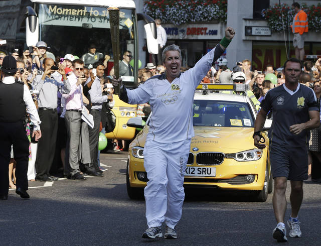Torchbearer Kevin Crain, carries the Olympic Flame as he arrives at St. Paul's Cathedral, in central London, ahead of the 2012 Summer Olympics, Thursday, July 26, 2012, The Olympic Torch is being carried around London in the final stages of a relay of torchbearers to make its way to the London 2012 Olympic Games opening ceremony on July 27, 2012. (AP Photo/Lefteris Pitarakis)