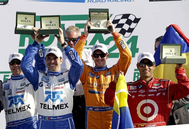 ADDS FIVE-TIME ROLEX CHAMPION HURLEY HAYWOOD -From left, Ganassi Racing team drivers Scott Pruett, Memo Rojas, of Mexico, Charlie Kimball and Juan Pablo Montoya, of Colombia, hold up their Rolex watches given to them for winning the Grand-Am Series Rolex 24 hour auto race at Daytona International Speedway, Sunday, Jan. 27, 2013, in Daytona Beach, Fla. Five-time Rolex champion Hurley Haywood, background center, looks on. (AP Photo/John Raoux)