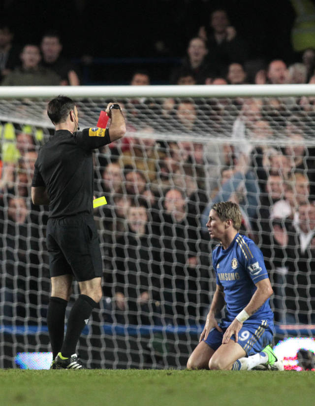 Chelsea's Fernando Torres, right, is being shown a red card by referee Mark Clattenburg after his second booking during their English Premier League soccer match against Manchester United at Stamford Bridge, London, Sunday, Oct. 28, 2012. (AP Photo/Sang Tan)