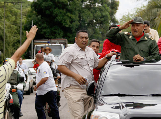 Venezuela's President Hugo Chavez, right, greets supporters upon his arrival to La Fria, Venezuela, Thursday, Oct. 20, 2011. Chavez said he is cancer-free because a series of medical exams in Cuba showed no recurrence of the illness following two months of chemotherapy treatments. Chavez underwent surgery in Cuba in June to remove a cancerous tumor from his pelvic region. He has not revealed where the tumor was located nor the type of cancer with which he was diagnosed. (AP Photo/Fernando Llano)