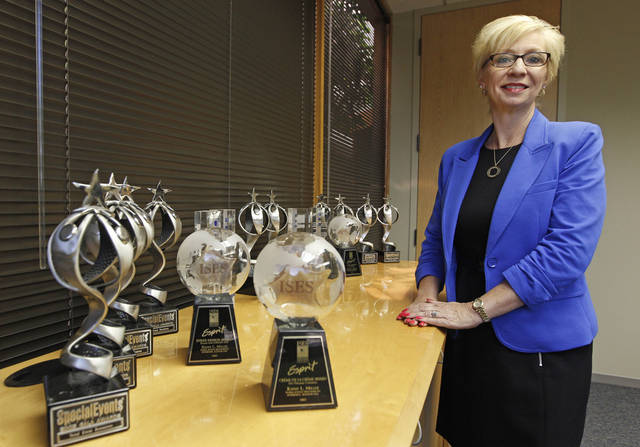 "In this Friday, June 15, 2012 photo, Kathy Miller, president of Total Event Resources, poses for a photograph next to trophies awarded to her company in her offices in Schaumburg, Ill. In 2008, her events planning company was having its best year ever. She and her husband had set aside money to put their two sons through college, with enough left in savings for ""a very nice life"" in the Chicago suburb. Then the financial crisis sent the stock market tumbling and the corporate customers who had kept Miller's company busy, stopped calling. When the government reported that the Great Recession claimed nearly 40 percent of Americans' wealth, the figure alarmed economists. But for families across the country, the numbers merely confirm that they are not alone. (AP Photo/M. Spencer Green)"