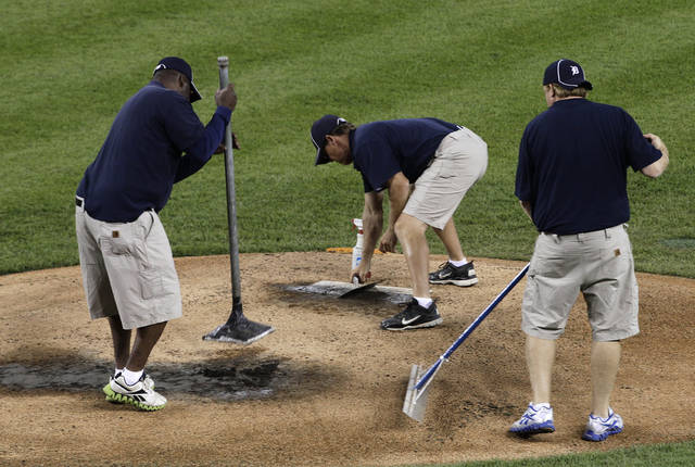 ADVANCE FOR WEEKEND EDITIONS, JUNE 9-10 - In this photo taken June 5, 2012, Comerica Park grounds crew work on the pitchers mound after the Detroit Tigers-Cleveland Indians baseball game in Detroit. In a game full of nuance, where no two ballparks look exactly alike, most fans might view the pitcher's mound as an afterthought. But although there are rules governing how mounds are set up, there is plenty of variance from ballpark to ballpark. (AP Photo/Paul Sancya)
