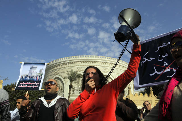 "An Egyptian protester shouts anti--President Mohammed Morsi slogans in front of the presidential palace in Cairo, Egypt, Friday, Jan. 25, 2013. Authorities expect a violent anniversary of the 2011 uprising that toppled long-time authoritarian President Hosni Mubarak. Arabic reads, ""save Egypt from the rule of the brotherhood leader."" and at left read ""from Assiut train accident to Badrasheen train accident, where are you?""  (AP Photo/Amr Nabil) ORG XMIT: AMR111"