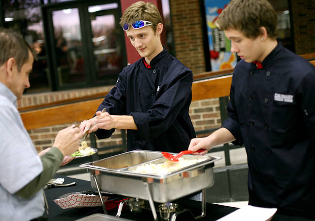 Putnam City West High School student Michael McQuaid serves food Tuesday.