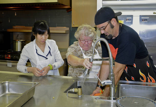 Frank Paradise Jr., Carolyn Sullivan and Meihua Guo help prepare food for the Edmond  Community Thanksgiving Dinner.  Photo by M. Tim Blake, for The Oklahoman &lt;strong&gt;M. Tim Blake&lt;/strong&gt;