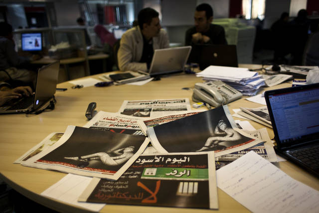 Egyptian journalists at the editorial room of Al-Masry Al-Youm daily newspaper next to copies of Egypt�s most prominent newspapers running black background front pages with Arabic that reads, �no to dictatorship, tomorrow free newspapers will obscure to protest the freedom's restrictions,� and a picture of a man wrapped in newspapers with his feet cuffed, in Cairo, Egypt, Monday, Dec. 3, 2012. Eleven Egyptian newspapers are planning to suspend publication on Tuesday to protest against President Mohammed Morsi's decision to call a constitution referendum on 15 December. (AP Photo/Nasser Nasser)