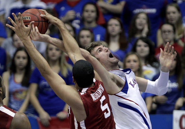 Oklahoma forward C.J. Washington (5) blocks a shot by Kansas forward Jeff Withey, right, during the second half of an NCAA college basketball game on Wednesday, Feb. 1, 2012, in Lawrence, Kan. Kansas won the game 84-62. (AP Photo/Charlie Riedel) ORG XMIT: KSCR111
