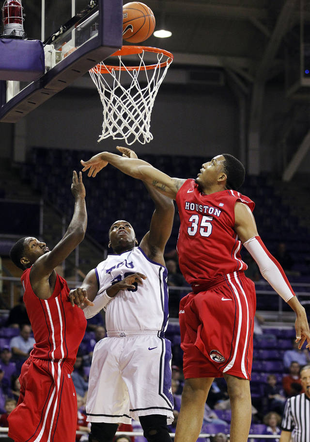 Houston's Mikhail Mclean, left, and Tashawn Thomas (35) defend against a shot by TCU's Devonta Abron during their NCAA college basketball game, Tuesday, Dec. 4, 2012, in Fort Worth, Texas. Houston won 54-48. (AP Photo/The Fort Worth Star-Telegram, Ron T. Ennis)  MAGS OUT; (FORT WORTH WEEKLY, 360 WEST); INTERNET OUT