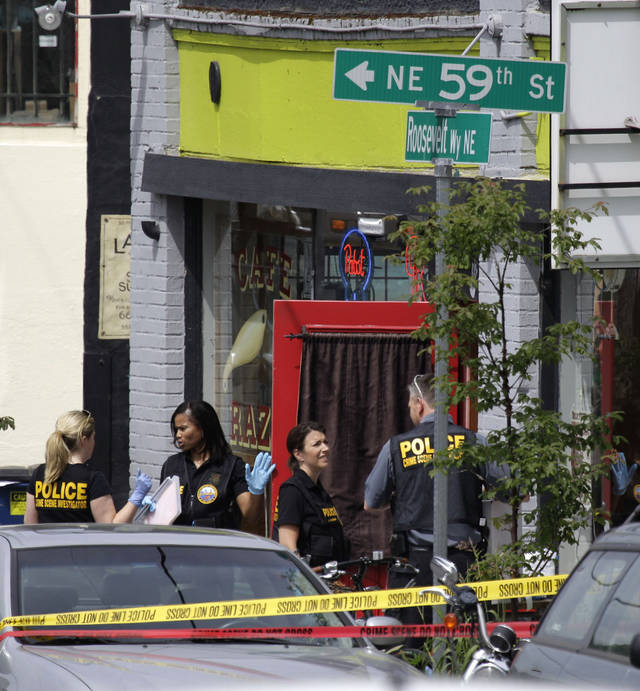 Seattle Police crime scene investigators process evidence outside a cafe where a shooting took place, Wednesday, May 30, 2012, in Seattle. A gunman earlier Wednesday killed two people and critically wounded three others at the cafe in Seattle's University District. (AP Photo/Ted S. Warren)