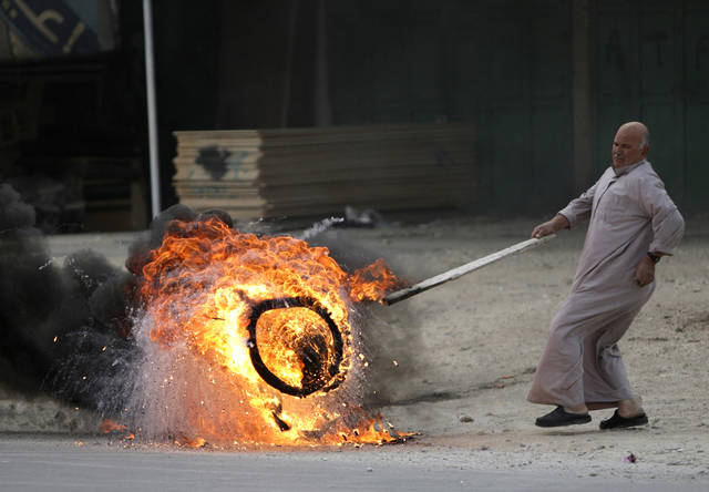 A man pushes a burning tire in the West Bank town of Nablus during a rally in support of Palestinian prisoners Friday, Feb. 22, 2013.  Israel holds a few thousand Palestinians on charges ranging from rock throwing to deadly attacks. (AP Photo/Nasser Ishtayeh)
