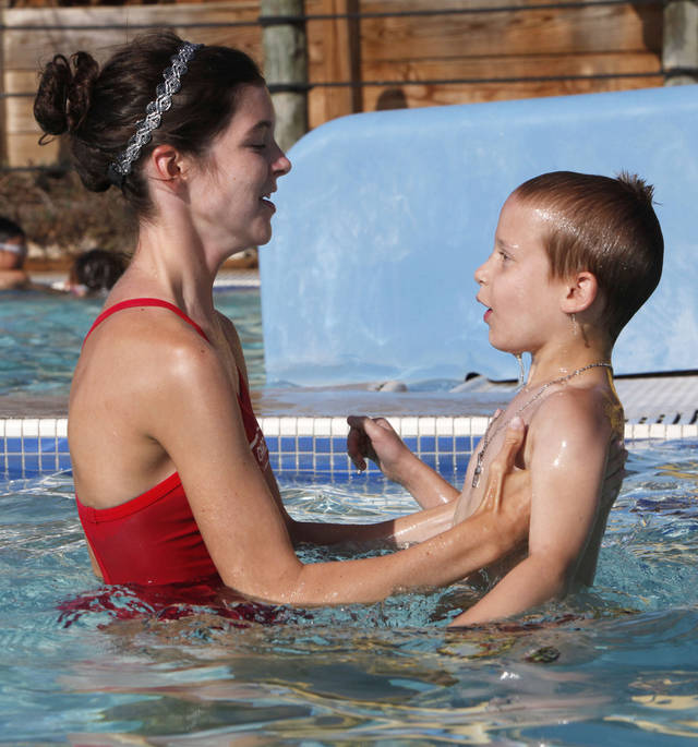 Instructor Elizabeth Wells lifts seven-year-old Bradley Gilliland out of the water during children's swim classes at Pelican Bay Aquatic Center in Edmond, OK, Tuesday, July 17, 2012,  By Paul Hellstern, The Oklahoman