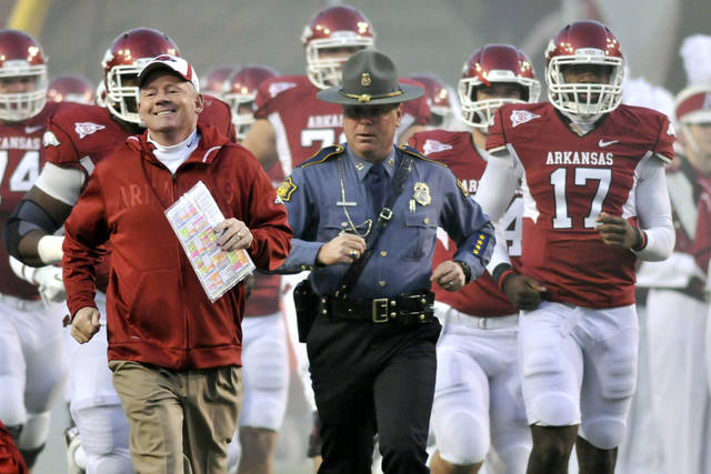 FILE - In this Nov. 12, 2011, file photo, Arkansas coach Bobby Petrino, left, followed by Arkansas State Police Captain Lance King, center, Brandon Mitchell (17) and and the rest of the team onto the field before the start of an NCAA college football game against Tennessee in Fayetteville, Ark. The Arkansas State Police are taking another look at the motorcycle crash involving coach Petrino. Authorities say they want to know how State Police Captain Lance King wound up meeting Petrino after the crash at an intersection in Fayetteville. King, who provides security for the coach during the season, then drove Petrino to a hospital. (AP Photo/April L. Brown, File)