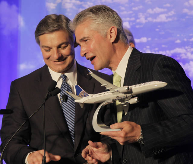 FILE -In this Thursday, July 12, 2012, file photo, United Airlines CEO Jeff Smisek accepts a a model of Boeing's new 737 Max 9 from Boeing Commercial Airplanes CEO Ray Conner, left, during a news conference, in Chicago.was a rough third quarter for United Airlines. United Airlines released its third quarter earning Thursday, Oct. 25, 2012, Travelers stayed away, frustrated by technology glitches from United's merger with Continental. And a huge accounting charge wiped out most of its profit. (AP Photo/M. Spencer Green, File)