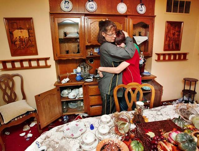 Tina Hackbarth hugs her daughter, Mercedes Oslin, 17, when Oslin began crying as she walked through the damage in her grandparents' dining room. An eathquake late Saturday night caused extensive damage to the two-story ranch-style home of Joseph and Mary Reneau near the community of Sparks in Lincoln County.  Contents inside their home were damaged earlier Saturday when an earthquake struck the same area.  Hackbarth is the Reneaus' daughter. Photo by Jim Beckel, The Oklahoman