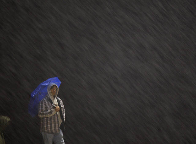 Standing in the rain, Millwood fan Mike Jorski watches the Class 2A high school football playoff game between Millwood and Lincoln Christian in Oklahoma City, Friday, Nov. 25, 2011. Photo by Bryan Terry, The Oklahoman