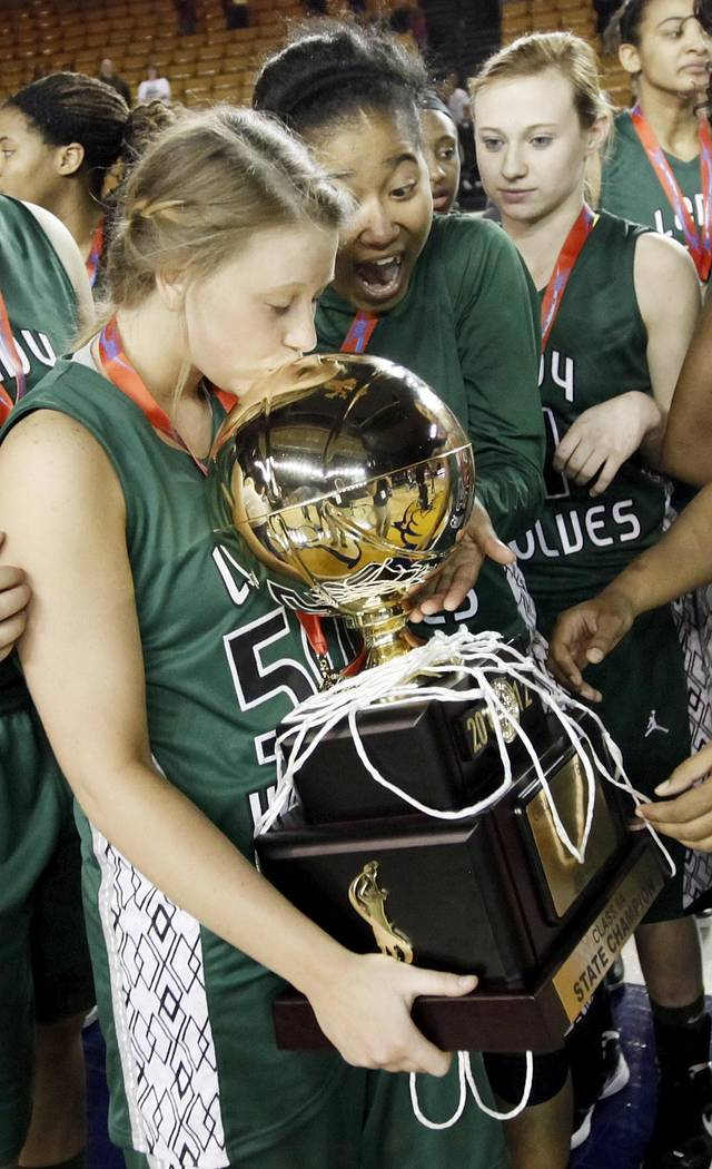 Edmond Santa Fe's Taylor Nashert (50) kisses the gold ball championship trophy as Tamara Lee (20), middle, and Jobi Heath (4) look on after the Class 6A girls high school basketball state tournament championship game between Edmond Santa Fe and Edmond Memorial at the Mabee Center in Tulsa, Okla., Saturday, March 10, 2012. Santa Fe won, 44-41. Photo by Nate Billings, The Oklahoman