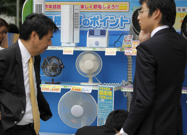 <p>Businessmen check electric fans on display at an electronics retailer in Tokyo Friday, July 1, 2011. The spokesman of the retailer said fan became a big seller since the March 11 earthquake and tsunami. Japan's government began imposing energy restrictions on companies, shopping malls and other major electricity users on Friday to cope with power shortages following the country's nuclear crisis. (AP Photo/Shuji Kajiyama)</p>