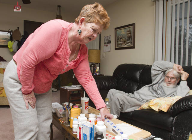 In this March 1, 2013 photo, Sandy Olger reaches for medication in the living room of the home she and her newlywed husband Jerry share in Milford, Mich.. Both Sandy and Jerry are dealing with significant illnesses. Sandy has multiple sclerosis and Jerry is combating a meningitis infection. (AP Photo/Livingston County Daily Press & Argus, Gillis Benedict) NO SALES
